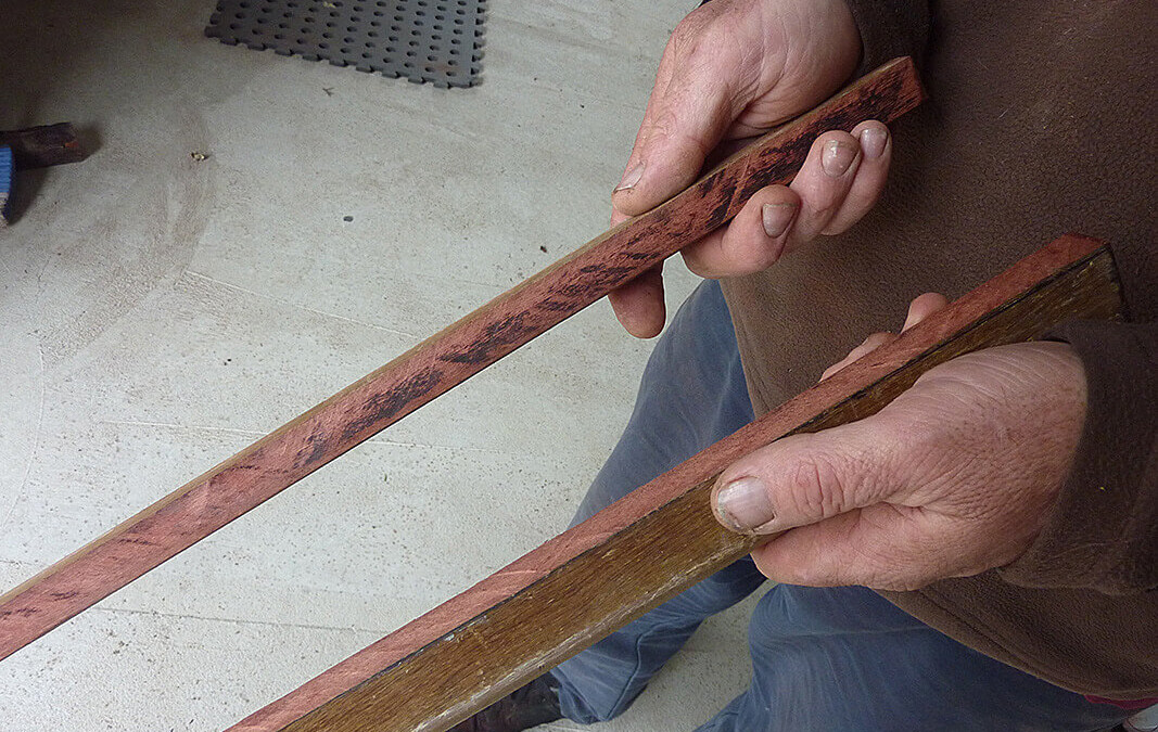 Photo of the framer's hands holding a recycled Jarrah skirting board sawn in half to show the beauty of the timber underneath the old varnish.